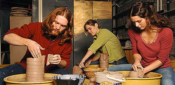 Two art students and a professor mold clay vases on the new pottery wheels in the UMD ceramics studio.