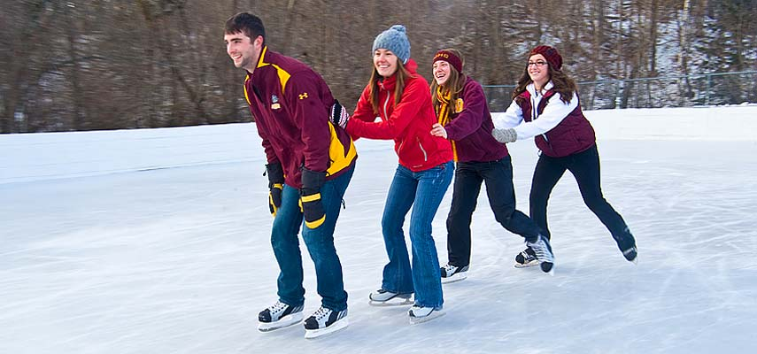Students skating outside on an ice rink.