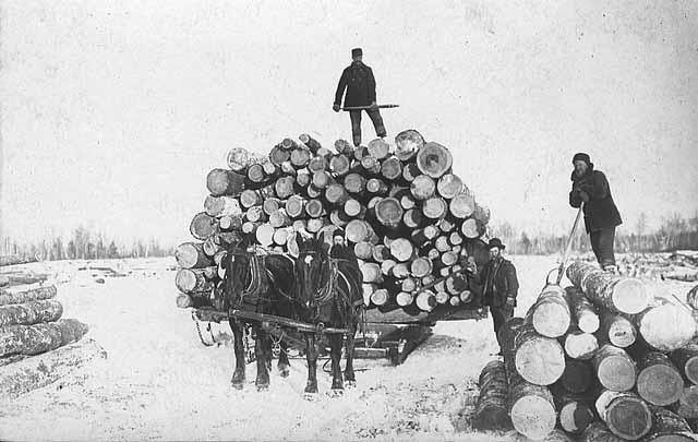 Crew with loaded sled of logs.