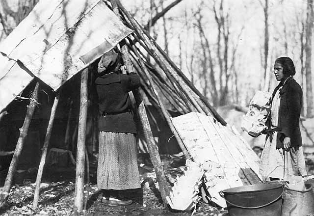Mrs. John Door and Anna Davis Door Building a birch bark tepee at maple sugar