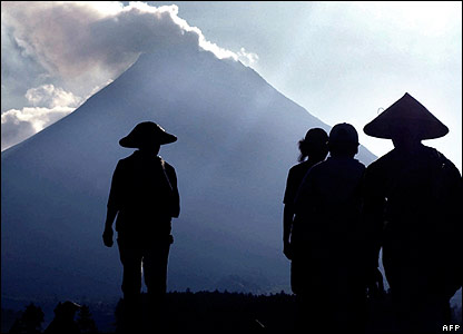 Java farmers silhouetted against volcanic Mount Merapi.