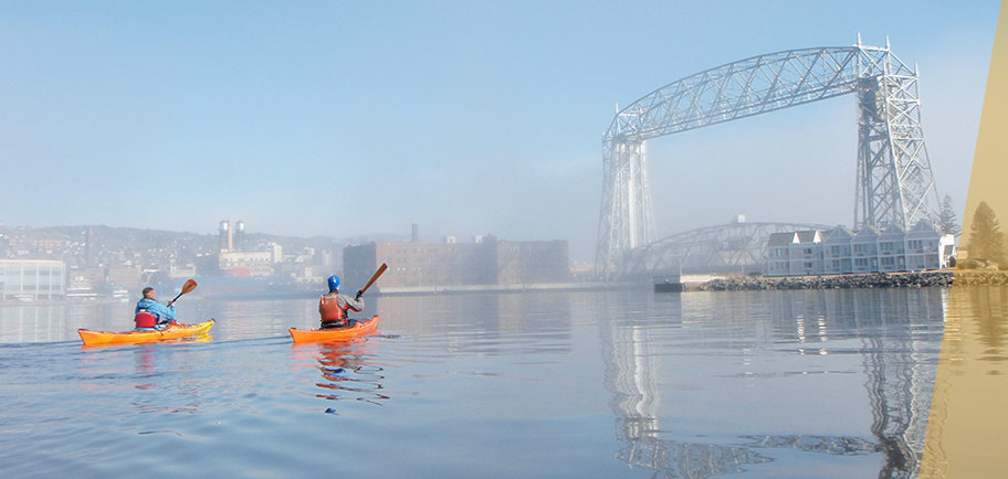 Two kayakers paddeling towards the Aerial Lift Bridge in the Duluth harbor.